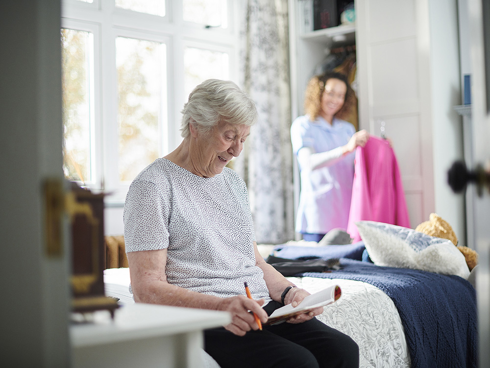 home carer helping assisted living senior woman get dressed in her bedroom